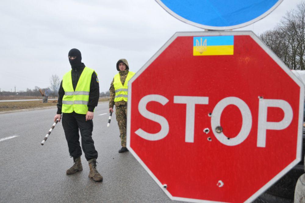 Украинские активисты стоят на блокпосту возле Львова, блокируя движение грузовиков с российскими номерами во Львовской области.