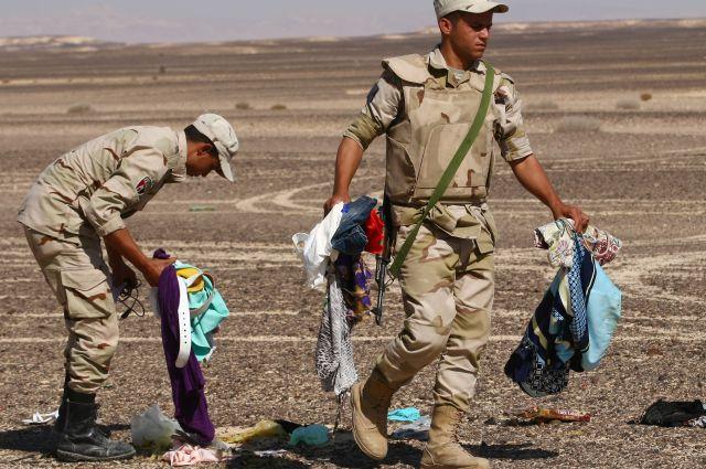 Военнослужащие Египта собирают личные вещи пассажиров на месте крушения Airbus A321