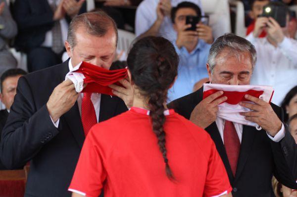 Президент Северного Кипра Мустафа Акынджи и президент Турции Тайип Эрдоган целуют турецкий флаг на торжественной церемонии, посвящённой 41-й годовщине со дня основания Турецкой Республики в Северном Кипре, 20 июля 2015.