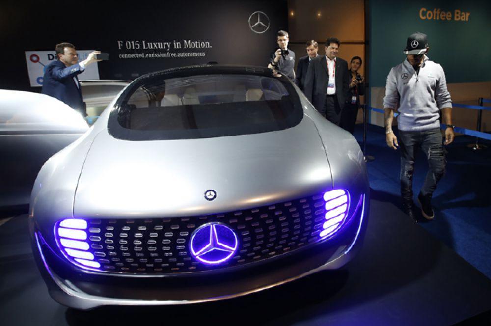 Гонщик «Формулы-1» Льюис Хэмилтон смотрит на автомобиль Mercedes 015 F.