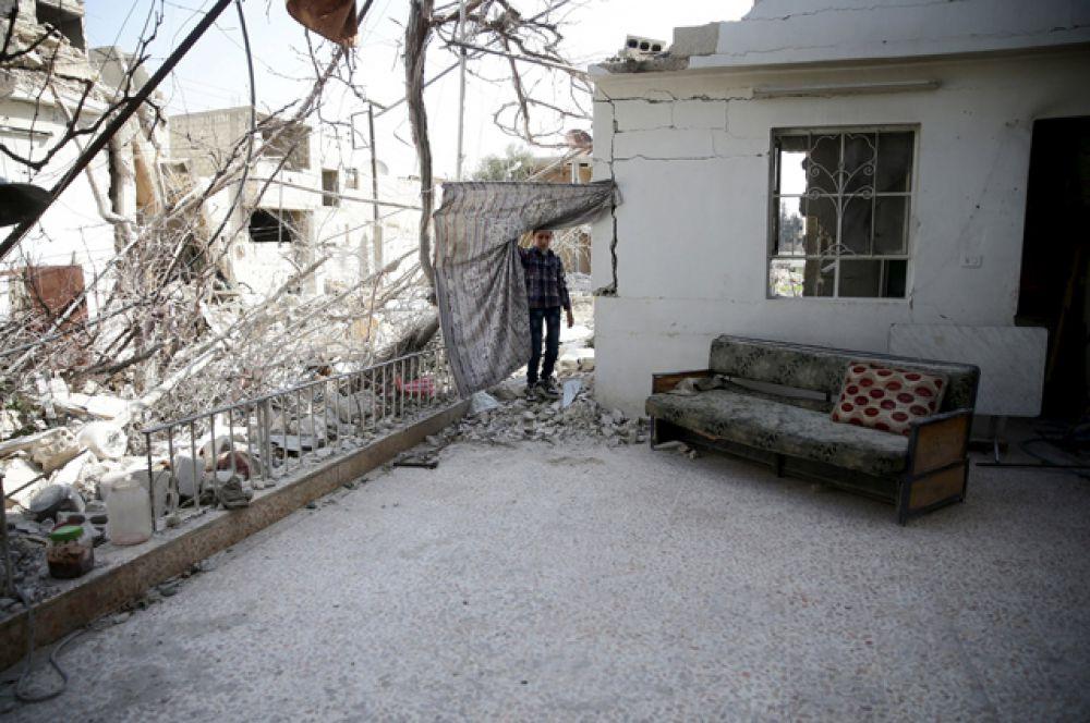 Мальчик осматривает разрушенный дом в Думе, Дамаск.