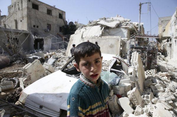 Мальчик на фоне разрушенных зданий в городе Дума, Дамаск.