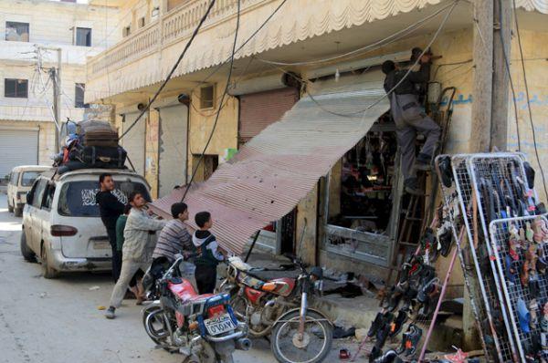 Жители ремонтируют поврежденный магазин в городе Дарат Изза на северо-западе Алеппо.