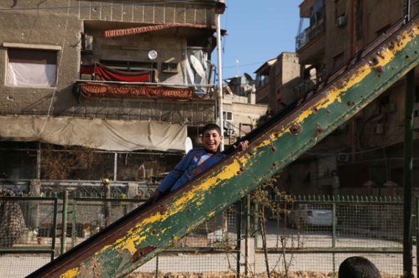 Дети играют на детской площадке в Думе, Дамаск.