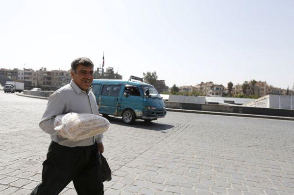 Мужчина с мешком хлеба на одной из окраин Дамаска.