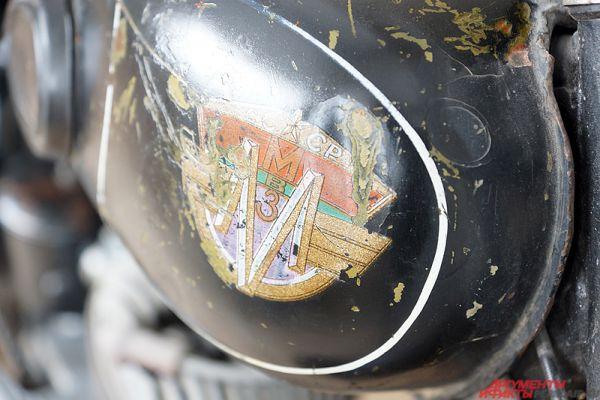 Потёртая эмблема на старом мотоцикле.