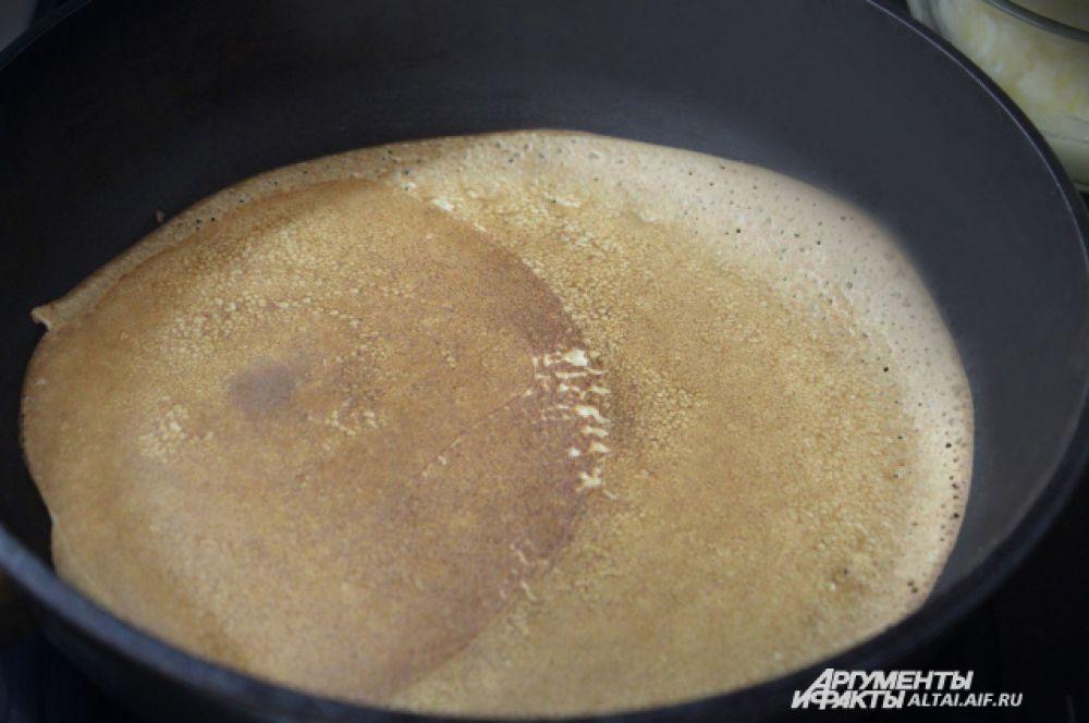 Как только блин будет легко отходить от сковороды, переворачиваем его на другую сторону и печем до готовности.
