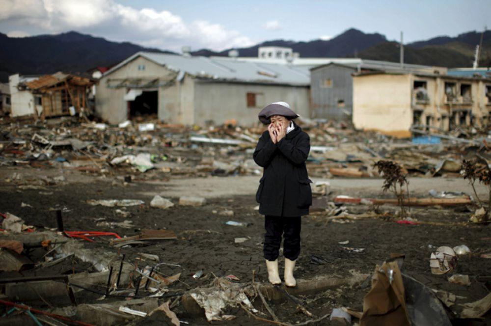 Женщина возле своего дома, разрушенного в результате землетрясения и цунами, в городе Кесеннума, 28 марта 2011 года.