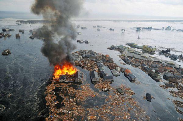 Жилые дома, уносимые водой после цунами и землетрясения в городе Натори, 11 марта 2011 года.