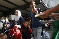 Местные жители Мюнхена раздают еду прибывшим беженцам из Сирии на центральном железнодорожном вокзале в Мюнхене.