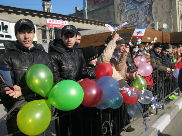 Школьники встречают колонну воздушными шарами, цветами и флагами