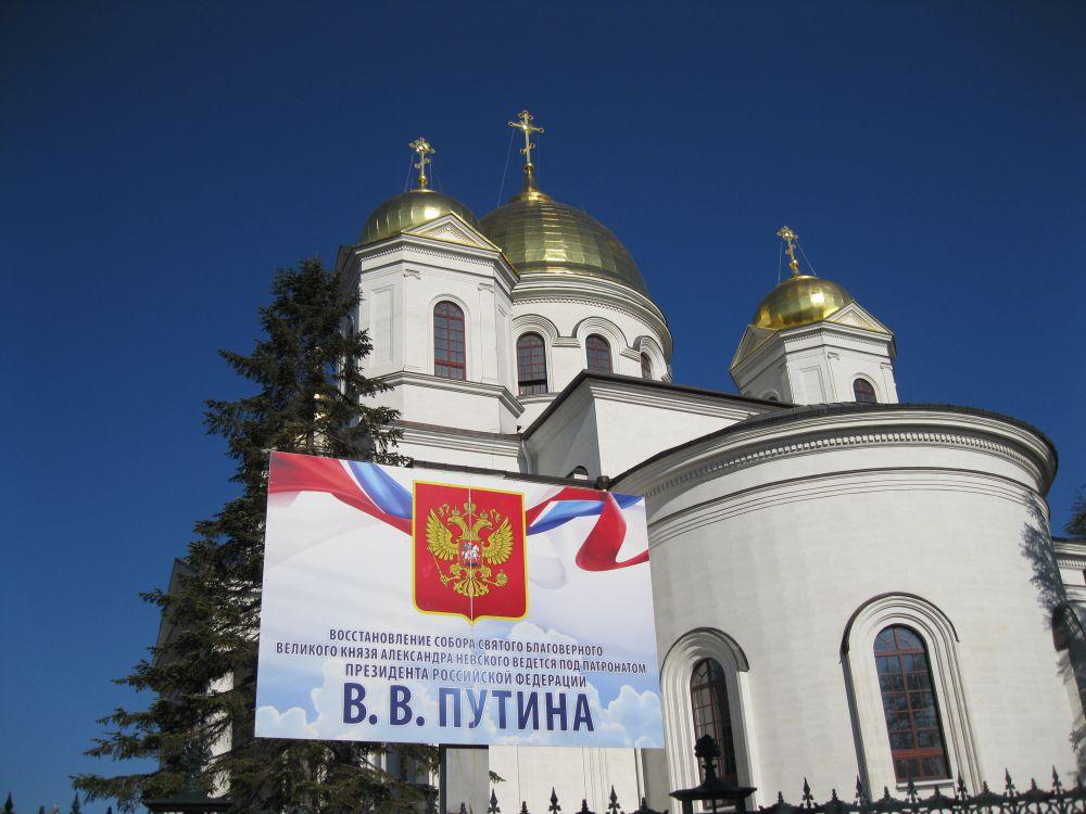 Колонна проходит мимо Александро-Невского собора, восстановление которого ведется под патронатом президента РФ Владимира Путина
