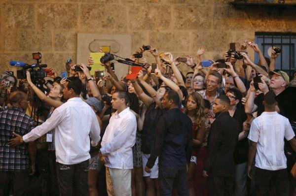 Метсные жители и туристы фотографируют приезд американского президента.