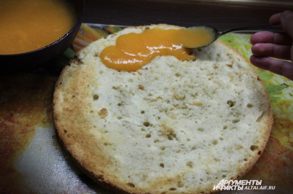 На бисквит наносим персиковое пюре и тонкий слой взбитых сливок.