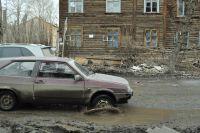 Лужи, ямы и грязь - привычная картина на омских дорогах.