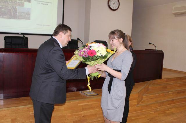 Генеральный директор РНПК Владимир Абрамов вручает заслуженные награды молодым специалистам.