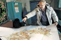 Фермер Николай Попов показывает на старой карте поля, которые сейчас заброшены.