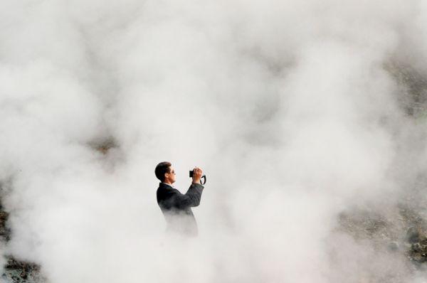 Один из туристов фотографирует пар в долин гейзеров на одном из склонов Мутновского вулкана.