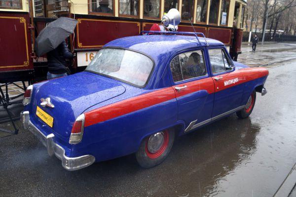 Колонну старинных и новых трамваев сопровождает ретро-автомобили милиции.