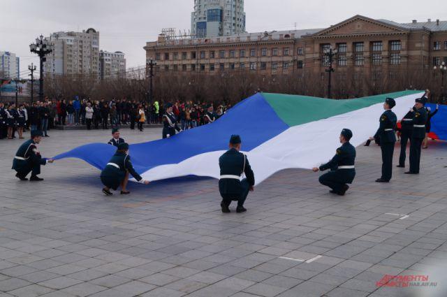 Группы школьников разворачивают флаг на главной площади Хабаровска.