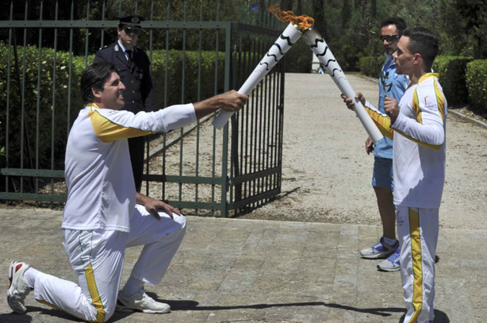 Затем спортсмен символически передал огонь бразильцу - двукратному олимпийскому чемпиону по волейболу Джоване Гавио.