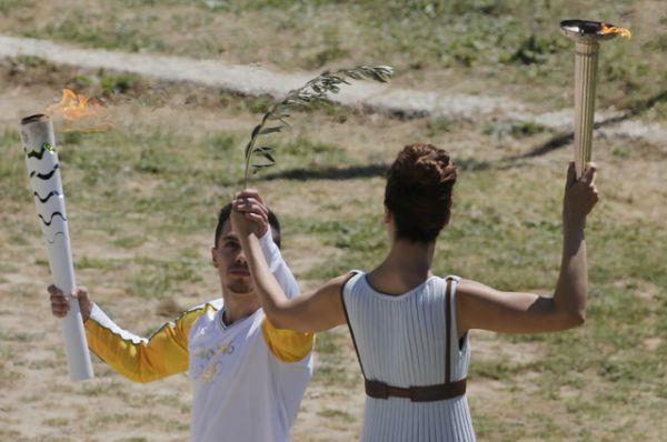 Катерина Леху передает Олимпийский огонь и оливковую ветвь первому факелоносцу - греческому гимнасту Элефтериосу Петруниасу.