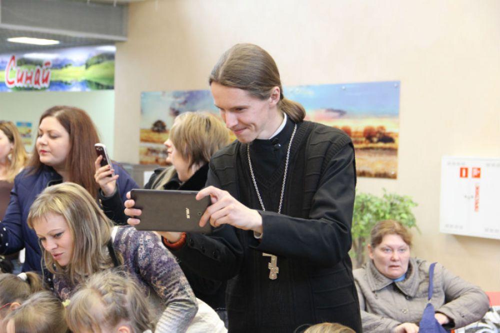 ...а отец Андрей тем временем фиксирует происходящее.