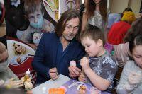 Никас Сафронов даёт детям мастер-класс по росписи пасхальных яиц.