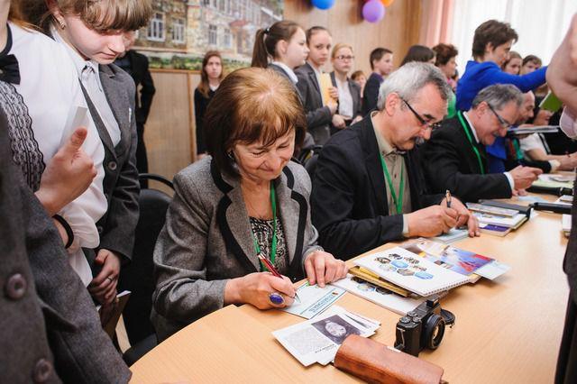 Члены делегации раздают автографы юным читателям.