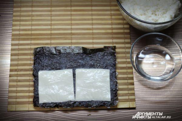 Аккуратно переворачиваем водоросль рисом на циновку так, чтобы полоска без риса оказалась вверху. Кладем пластинки плавленого сыра на нори.