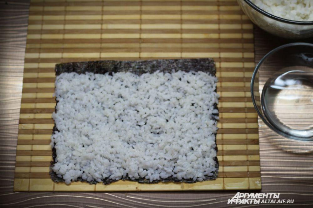 Равномерно выкладываем рис на нори, оставляем сверху полосу, примерно в один сантиметр без риса, для того чтобы ролл при сворачивании склеился.
