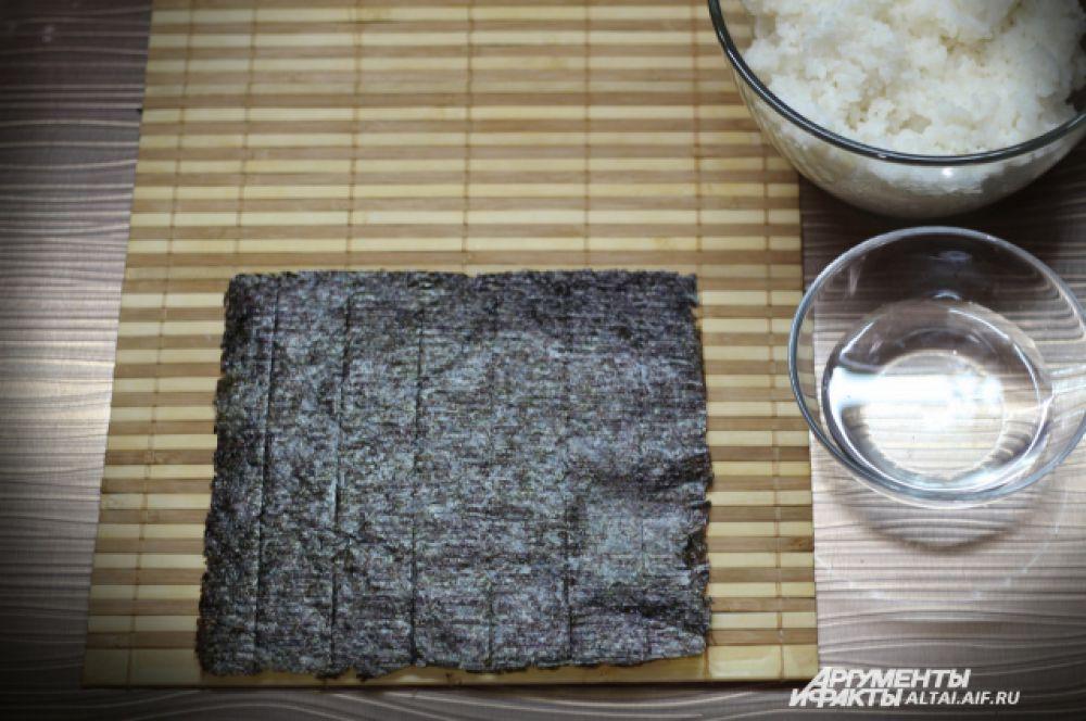 На сухую циновку кладем лист нори блестящей стороной вниз. В отдельную миску набираем кипяченой воды и добавляем в нее немного столового уксуса. Это нужно для того, чтобы смочить руки, тогда рис не будет к ним прилипать.