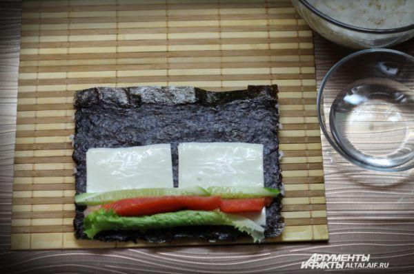 На сыр выкладываем форель, огурец и скрученный в трубочку салат.