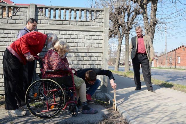 Члены общества «Мемориал» на глазах у чиновника замеряют высоту бордюра.