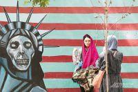 Туристы охотно фотографируются у здания бывшего посольства США.