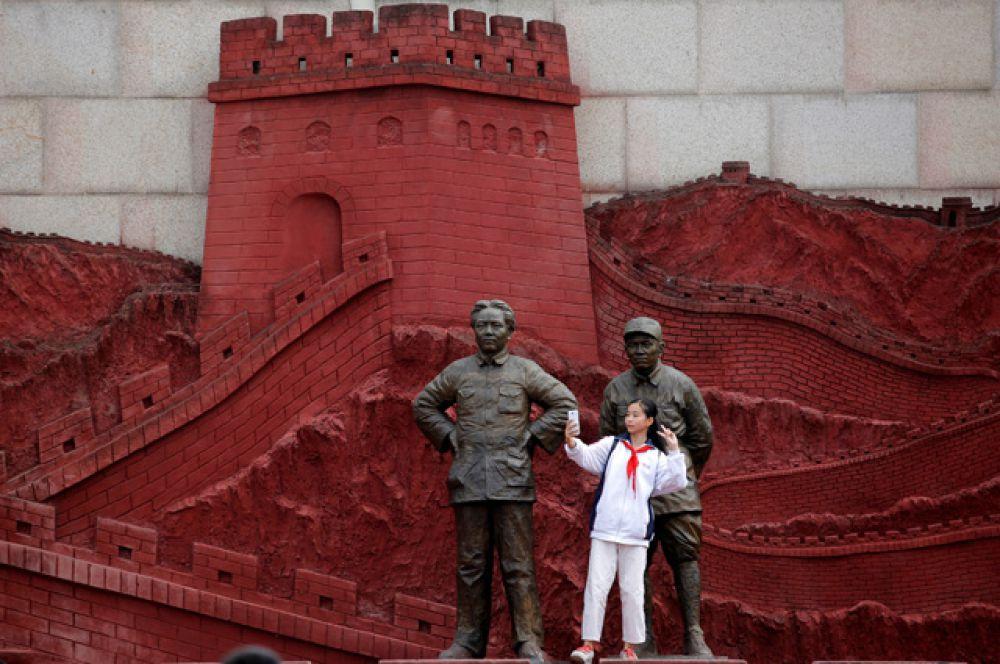 Девочка делает селфи с памятником Председателю Мао Цзэдуну и бывшему генералу Чжу Дэ.