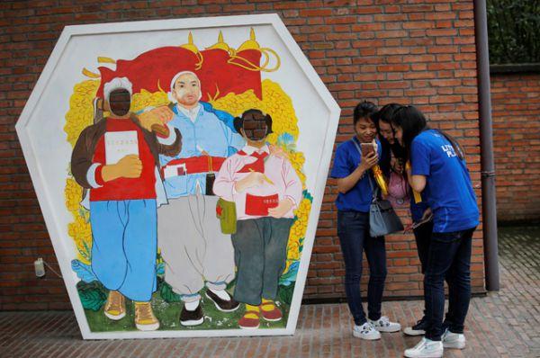 Посетители выставки фотографируются на фоне плаката того времени.