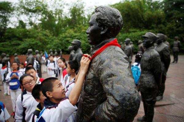 Школьники повязывают красный галстук на шею памятнику Мао.