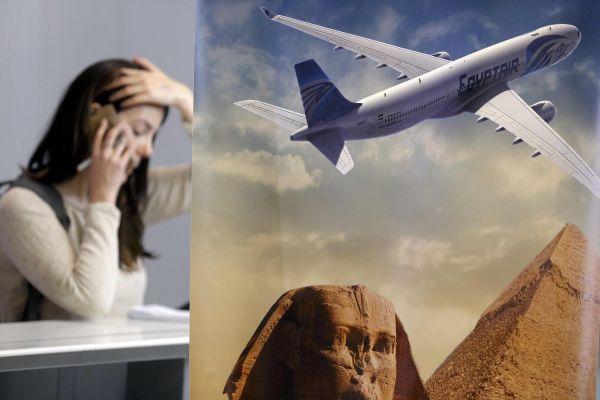 Журналистка разговаривает по телефону возле стойки компании EgyptAir в аэропорту «Шарль де Голль» в Париже.