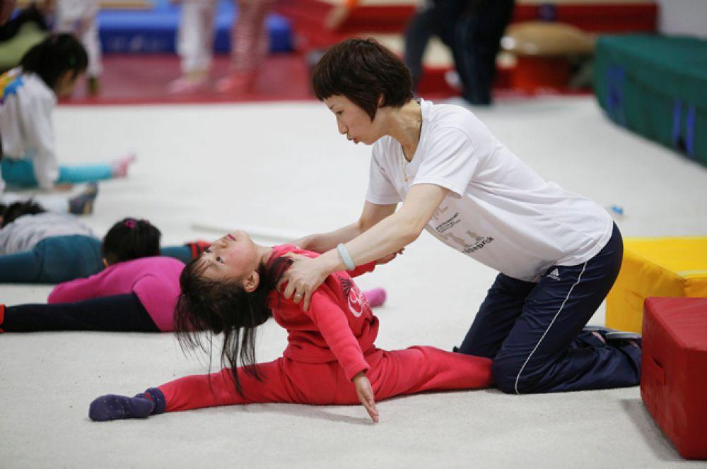 Тренер помогает девочке во время занятий гимнастикой.