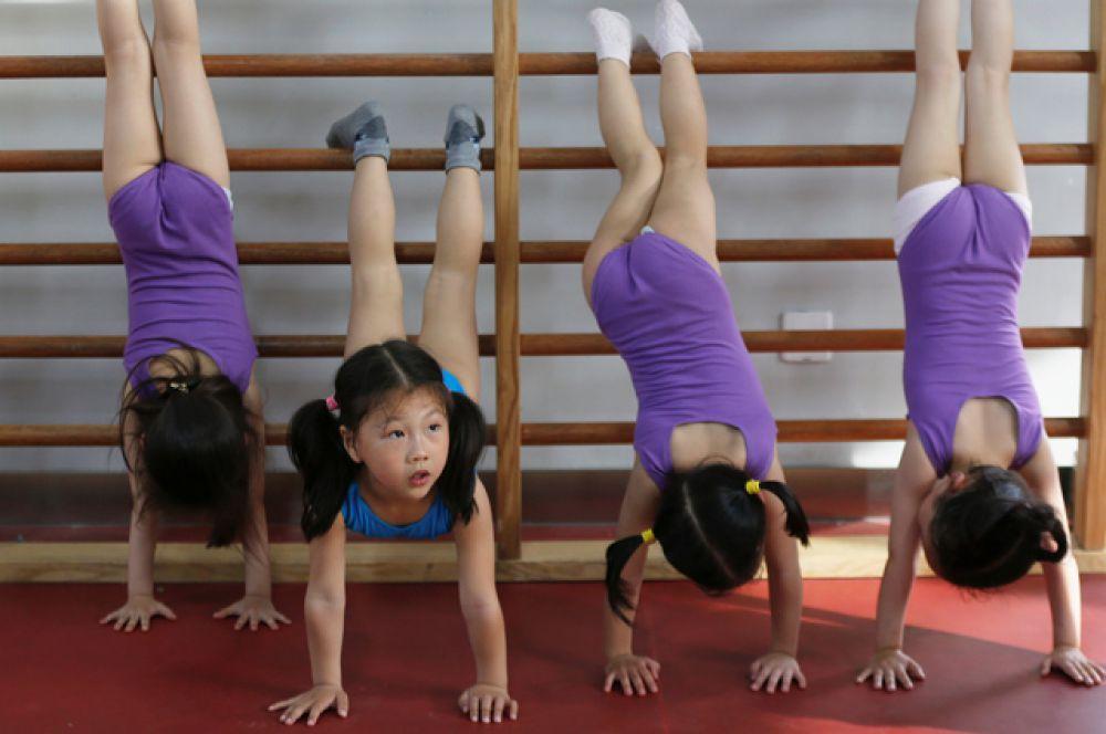 Дети практикуют стойку на руках.