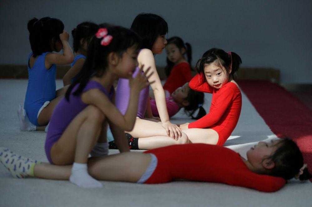 Девочки помогают друг другу во время занятий гимнастикой.