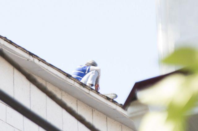 Увидев сидящего на краю крыши очевидцы заподозрили неладное