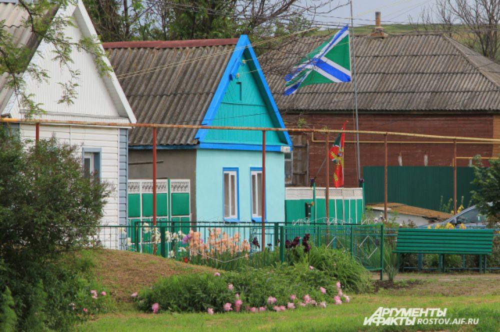 Российские флаги, олицетворяющие доблесть пограничников, вывешены во многих домах Русского.