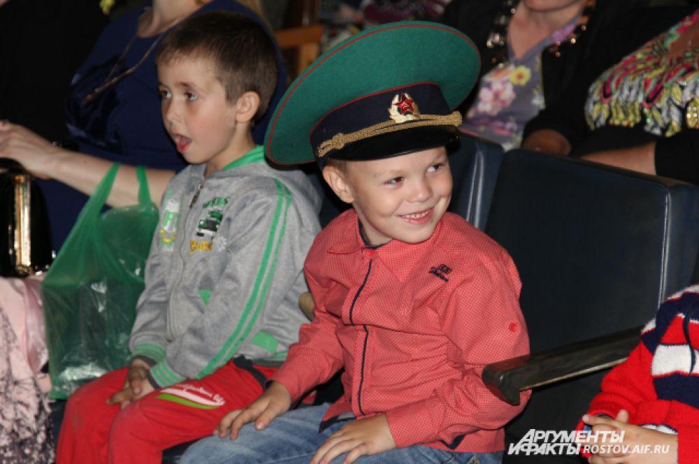 Дети и внуки пограничников смотрят концерт в зеленых фуражках родственников.