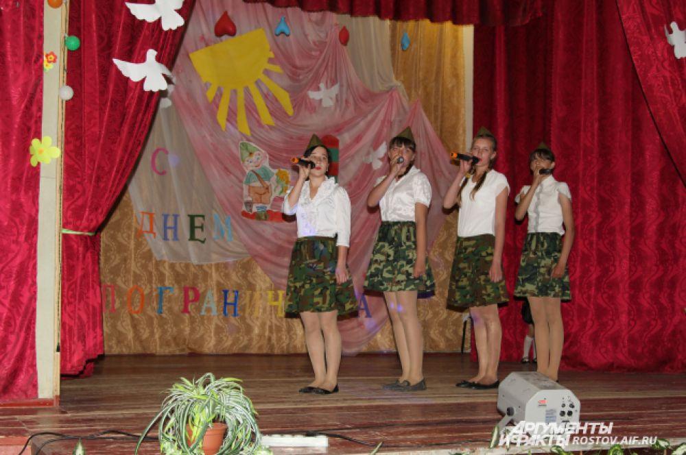 В сельском клубе Русского школьники своими силами поздравляют бывших пограничников. Они исполнили песни о пограничнике. Сцена украшена словами «С Днем пограничника!».