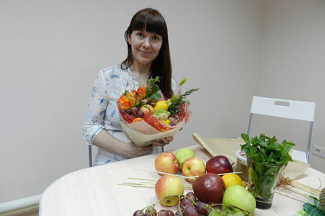 Людмила Лопаева создаёт очередной букет из фруктов.