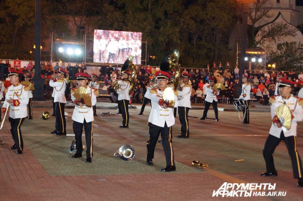 Музыканты Центрального оркестра вооружённых сил Сингапура лихо управляются с веерами.