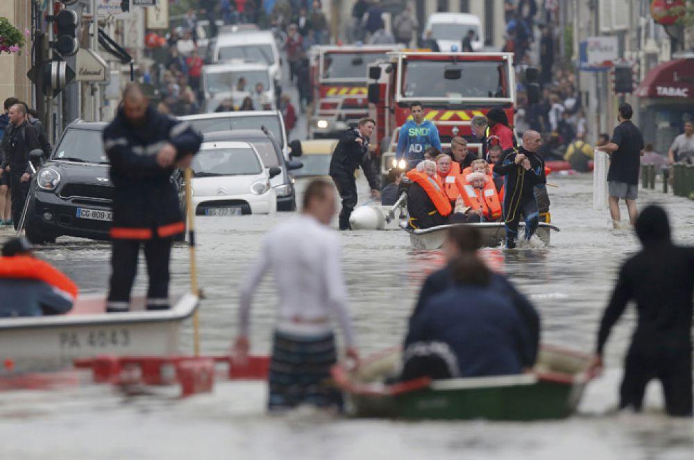 Спасатели эвакуируют жителей из затопленных площадей в одном из центральных районов Парижа.