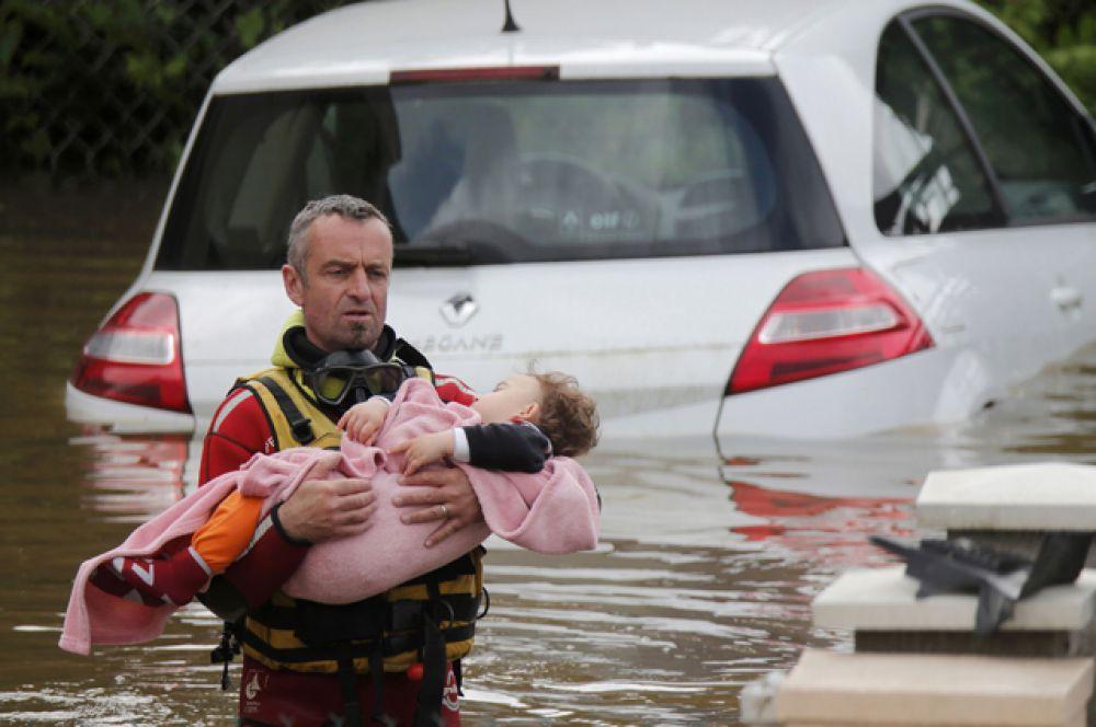 Спасатель выносит ребёнка на руках из затопленного района.